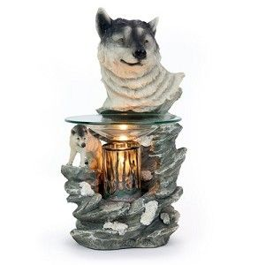 """$20.00    This oil warmer features the bust of a wolf with a wolf climbing the rocks below it. Glass dish holds the scented oil. Glass cylinder gives the warmer a unique look when the oil warmer is on. 35 watt halogen bulb heats the oil to release its scent. The power cord has a built in on/off switch and a dial to control the intensity of the heat. Measures approximately 8"""" h x 5"""" w"""