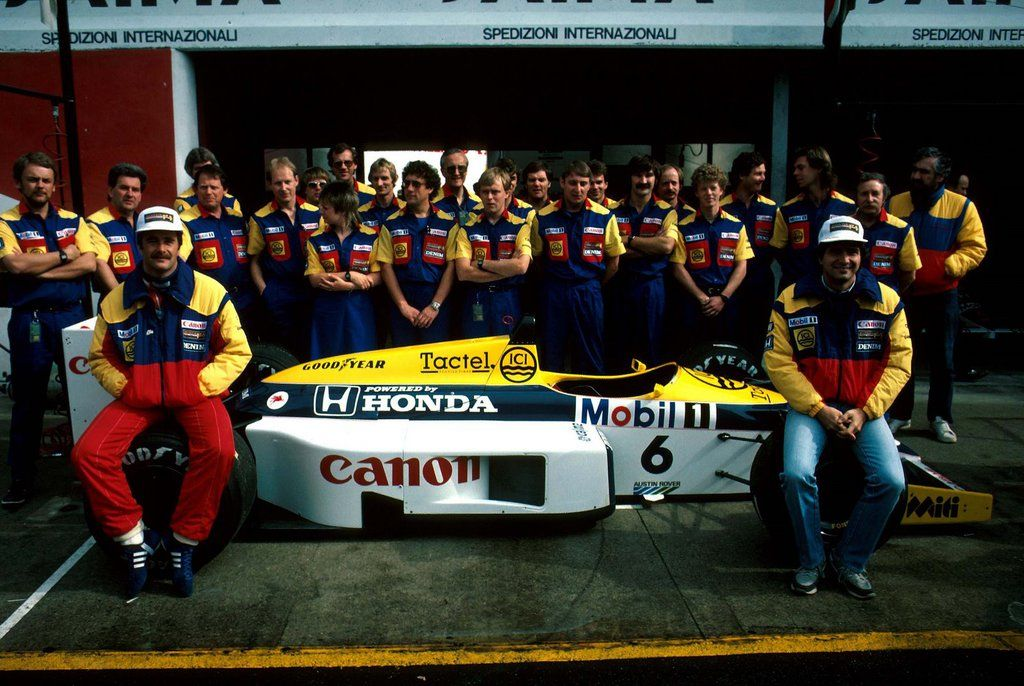 Williams team group shot featuring team members, the drivers Nigel Mansell (left) and Nelson Piquet (right) and Piquet's Honda-powered FW11,  1986