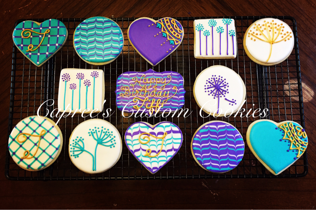 Custom purple, teal, and gold flower and heart cookies for a