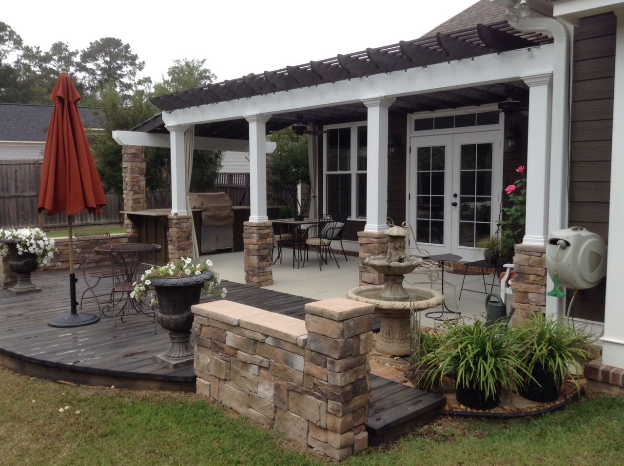 This craftsman style house backyard pergola grilling station sto