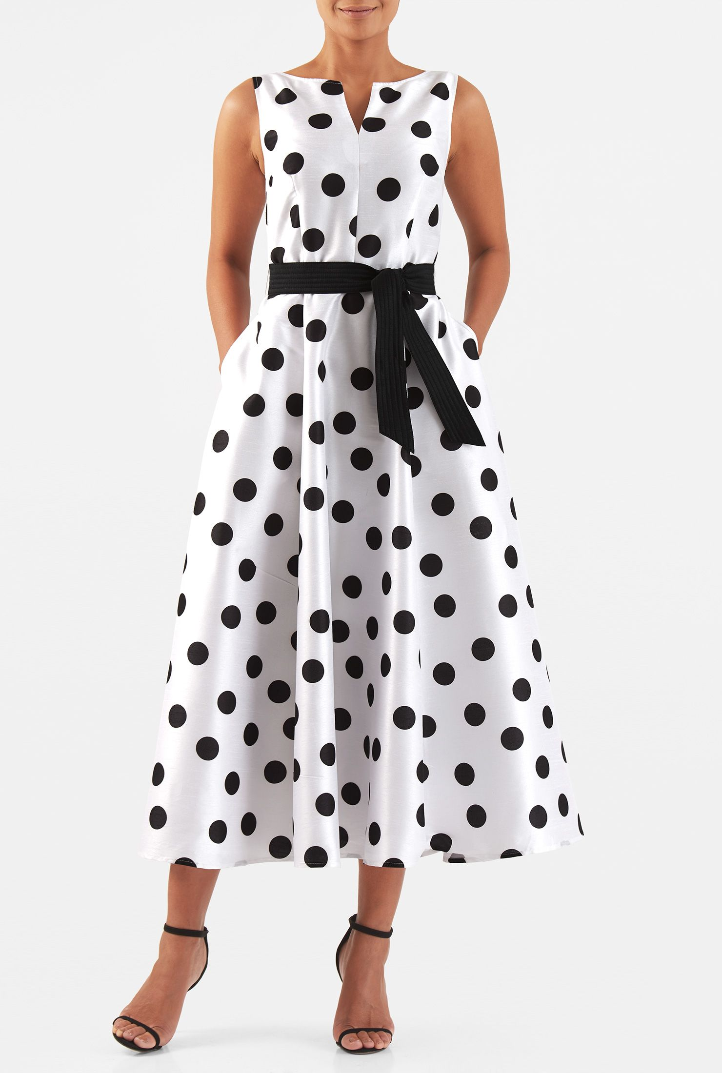 A split neck tops our polka dot print polydupioni dress designed with a fitted bodice and sash tied waist atop a full flared skirt.