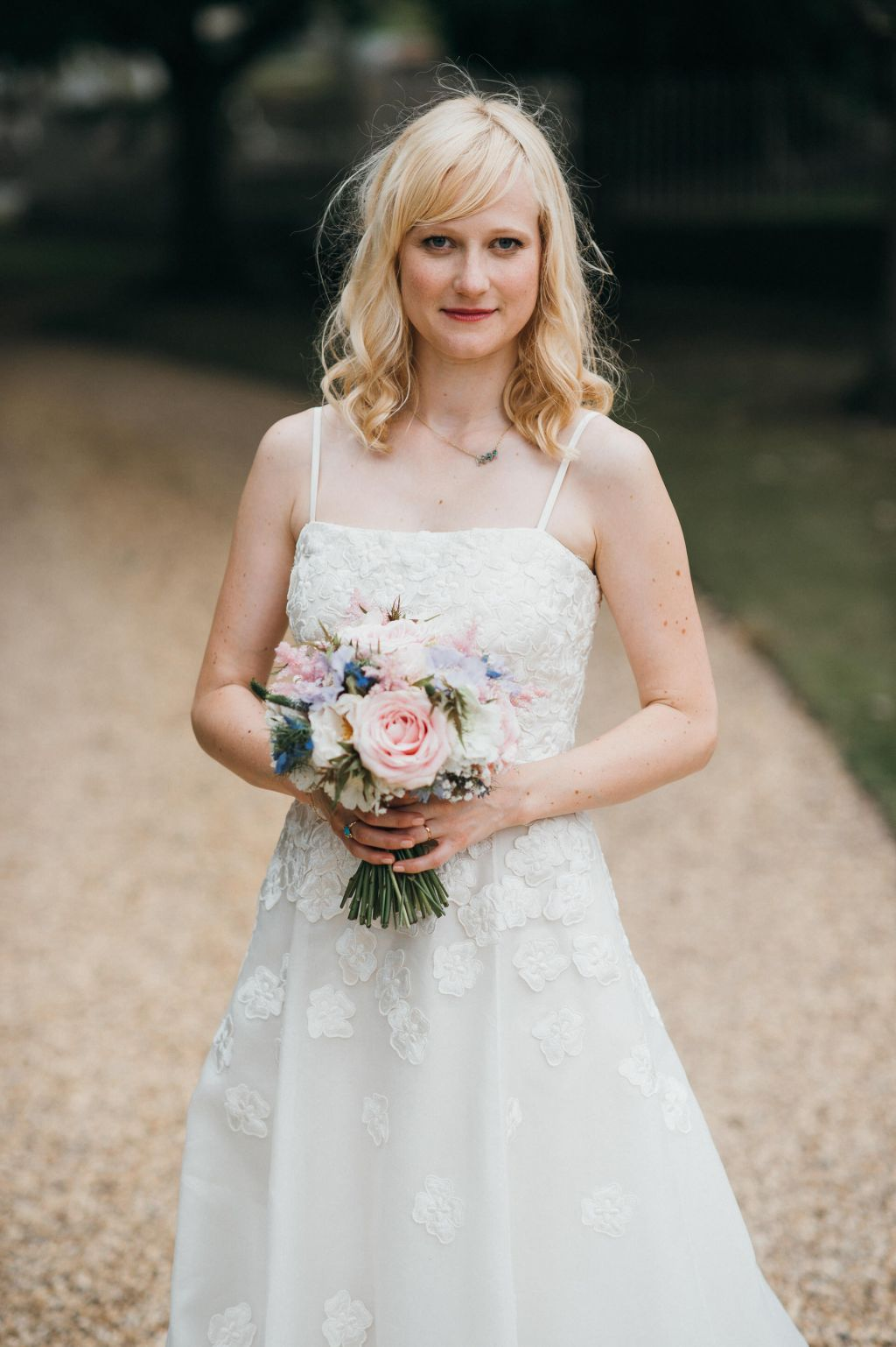 A simple ivory wedding dress with spaghetti straps at this Wiltshire wedding.