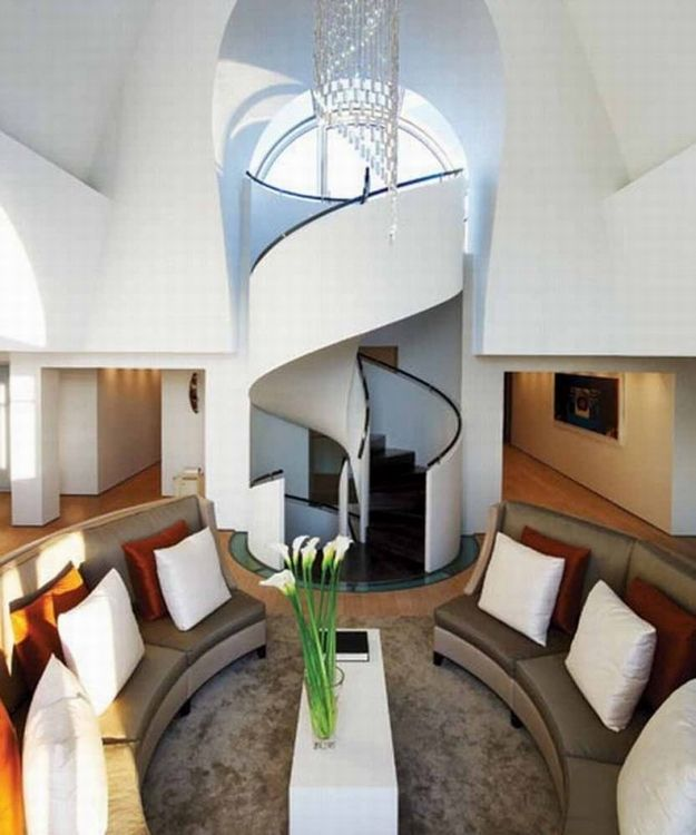 Love the circle effect with the staircase and couches... gotta have an awesome staircase