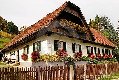 White Austrian Old Village House In Sumer Timewith Boxes With Geraniums On Windows
