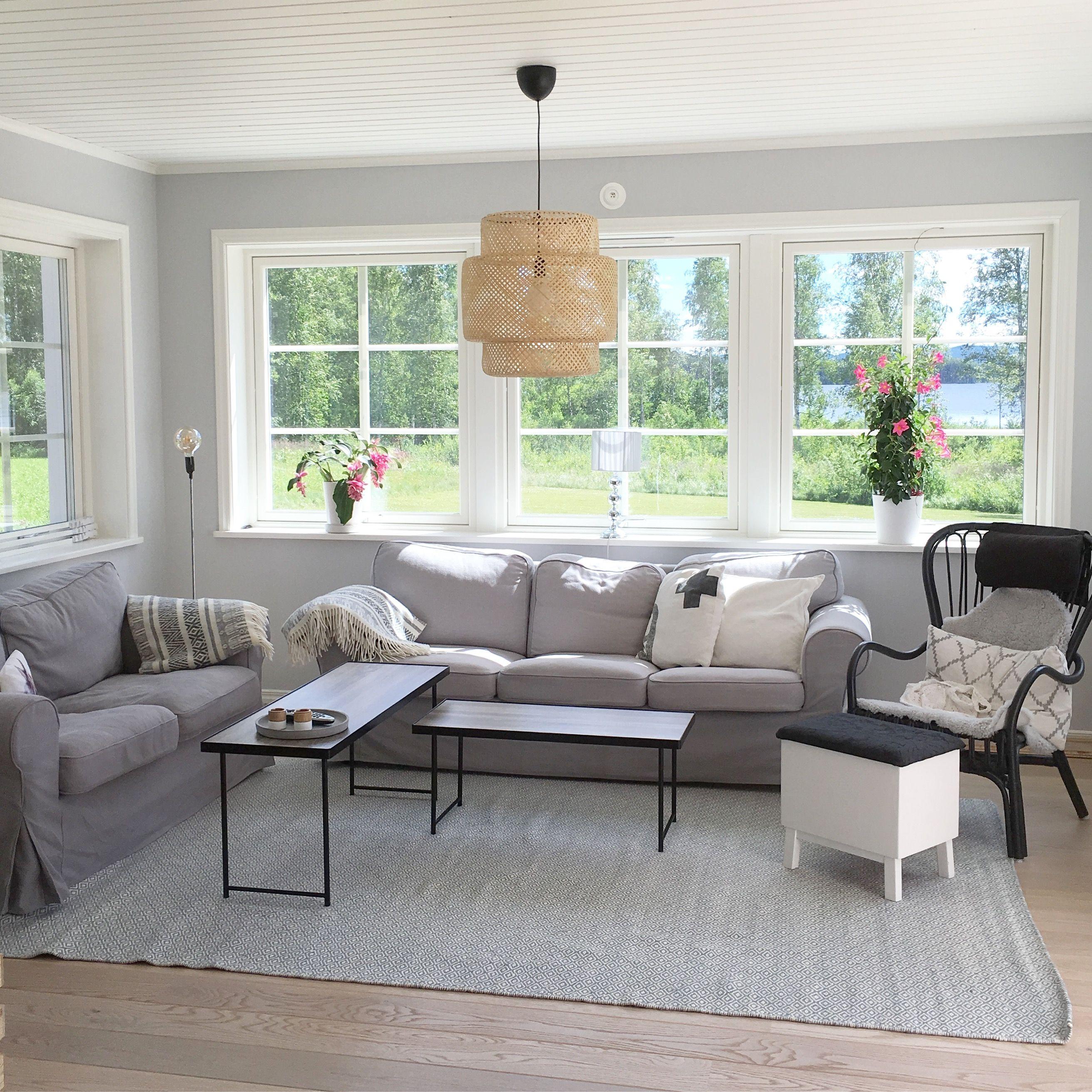 Grått vardagsrum med stora fönsterpartier och taklampa sinnerlig från Ikea