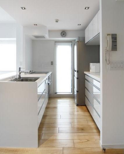 キッチンはペニンシュラ型で配置されており 鏡面仕上げの面材は高級感