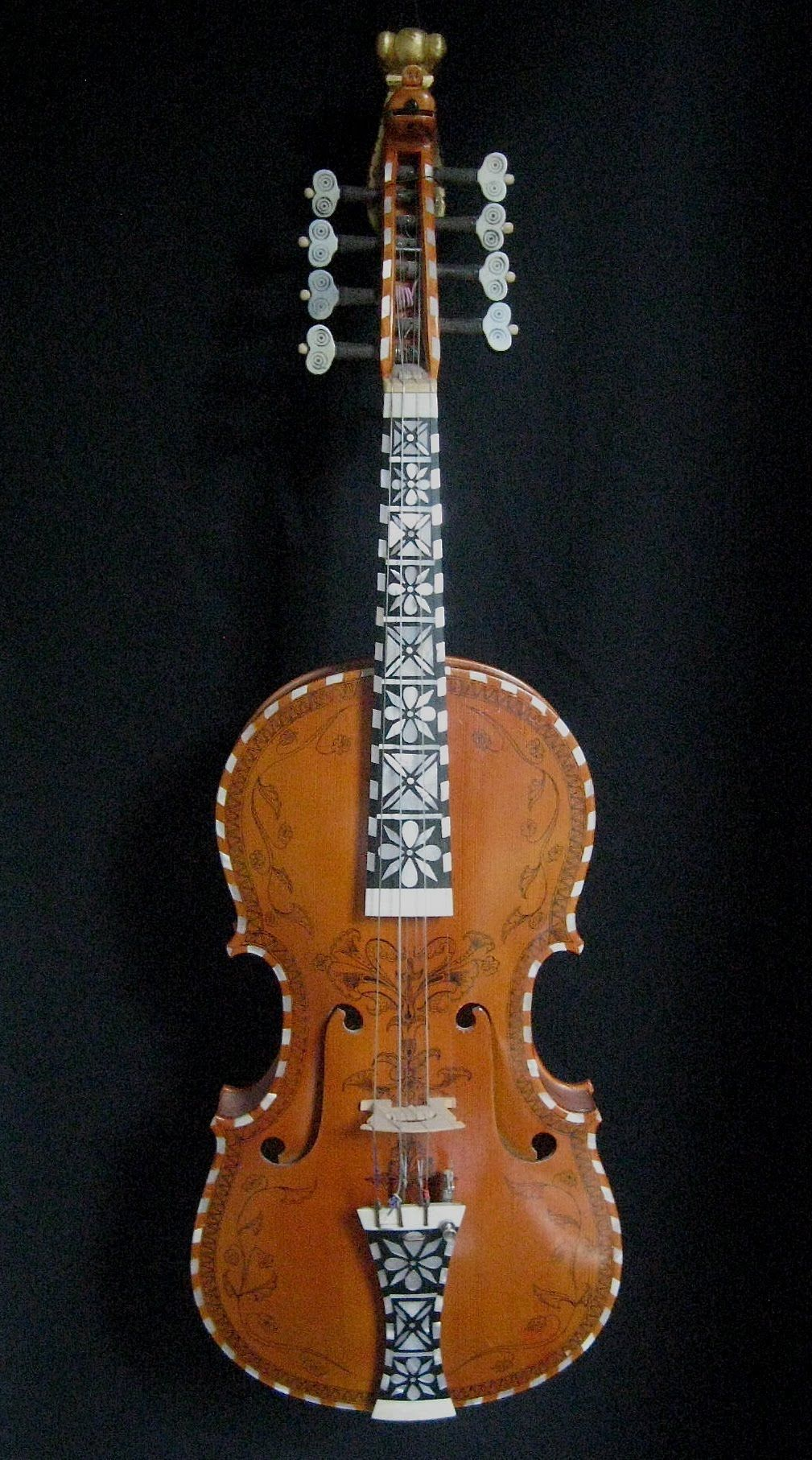 Hardingfele made by Lynn Berg - The Hardanger fiddle (in Norwegian, hardingfele) is often called the national instrument of Norway. It is similar to the violin and each one is a handmade work of art. A typical hardingfele is beautifully decorated with mother-of-pearl inlay and black pen-and-ink drawings, called rosing. It is topped with a carved head of a maiden (see photo below) or, more frequently, of an animal, usually a lion. Its most distinguishing feature is the four or five…