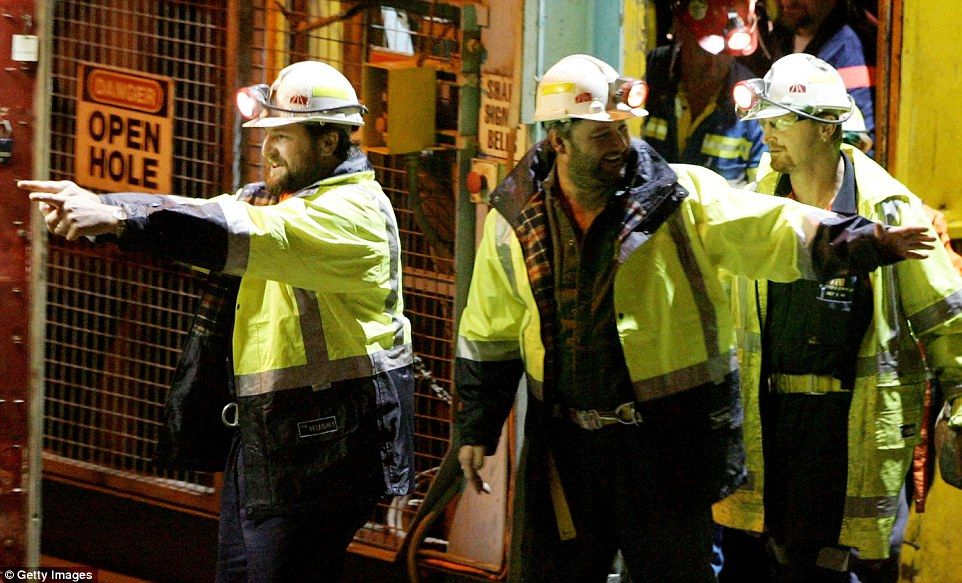 Tasmanian miners Todd Russell (left) and Brant Webb (centre) wave as they emerge from the mine lift having been rescued after being trapped underground at Beaconsfield gold mine for 14 days in 2006 after an earthquake caused a rock fall