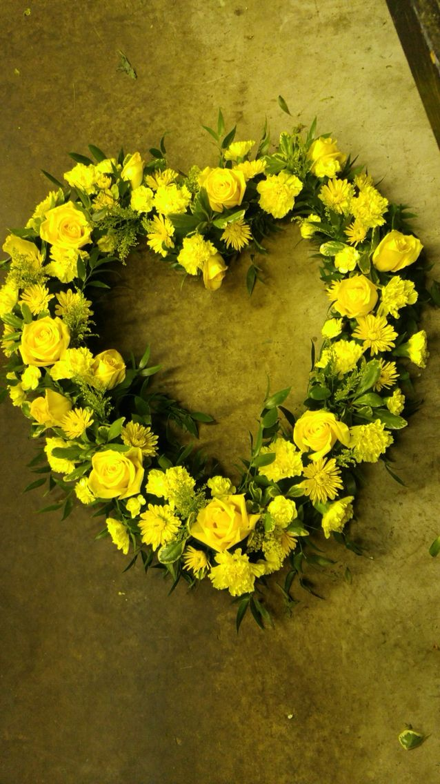 Heart shaped funeral spray for the service in yellow.  americasflorist.com