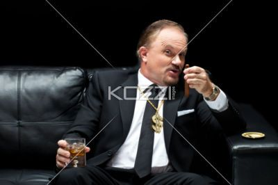 mature mafia boss with a glass of whiskey and a cigar. - Mature mafia boss with a glass of whiskey and a cigar sitting against black background, Model: Dan Sanderson
