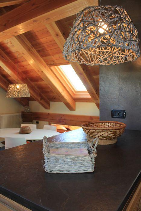 Casa di montagna. Lampade a sospensione in legno. Cucina e soggiorno. Top cuc...