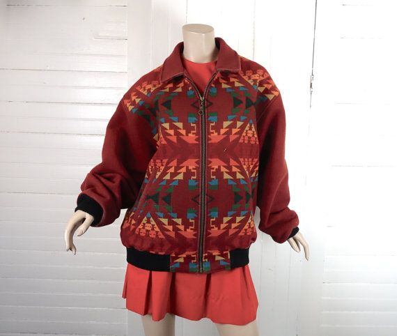 A bomber-style jacket from the 90s in rust red with a multi-colored southwest pattern. The fabric is heavyweight and woven, 87% wool and 13% cotton,