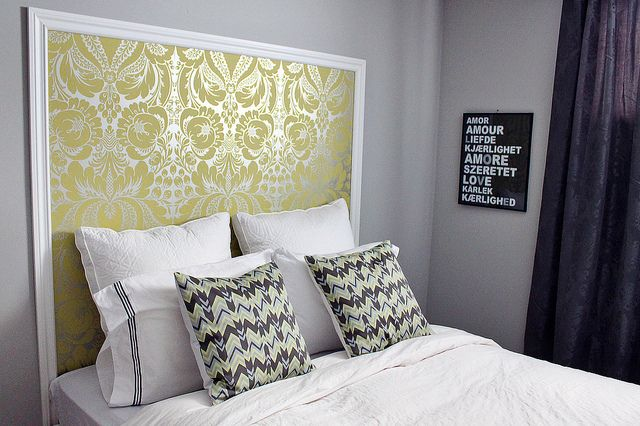 headboard on wall with molding and either stencil or wallpaper