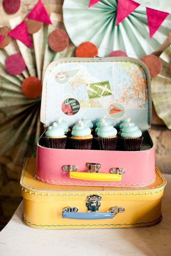 Pretty cupcakes sitting in colourful vintage suitcases for a travel themed wedding!: