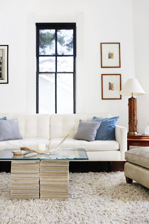 Bright, white living room and couch with blue pillows