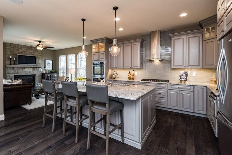 A stone fireplace adds warmth to this kitchen and hearth room. The Wyndham Heritage, a new home by Fischer & Frichtel in Ehlmann Farms. Weldon Spring, MO.