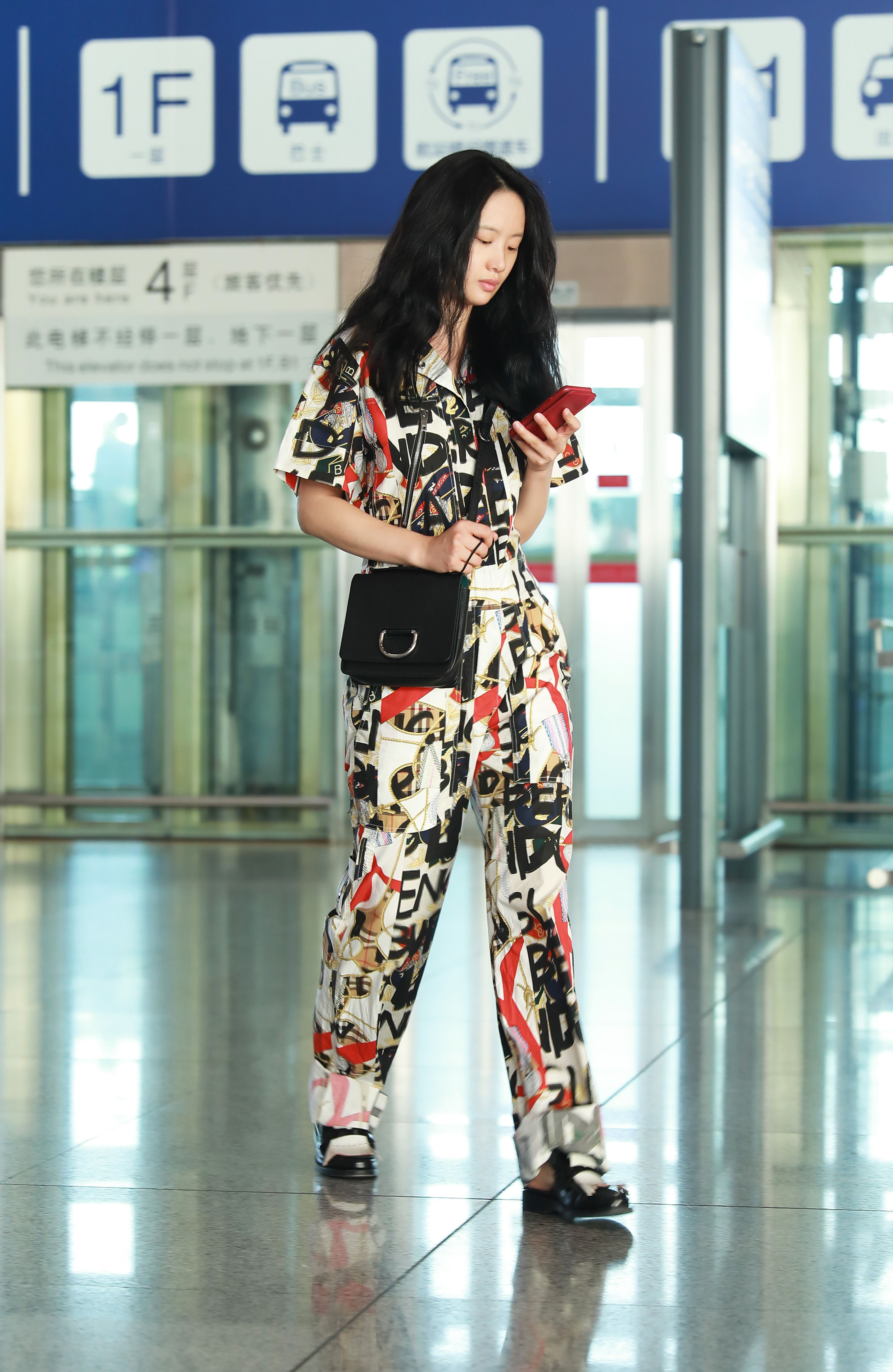c971f0f7bae4 Actress Vivien Li wearing  Burberry Graffiti Archive Scarf Print Jumpsuit  with the D-ring Bag at Beijing airport
