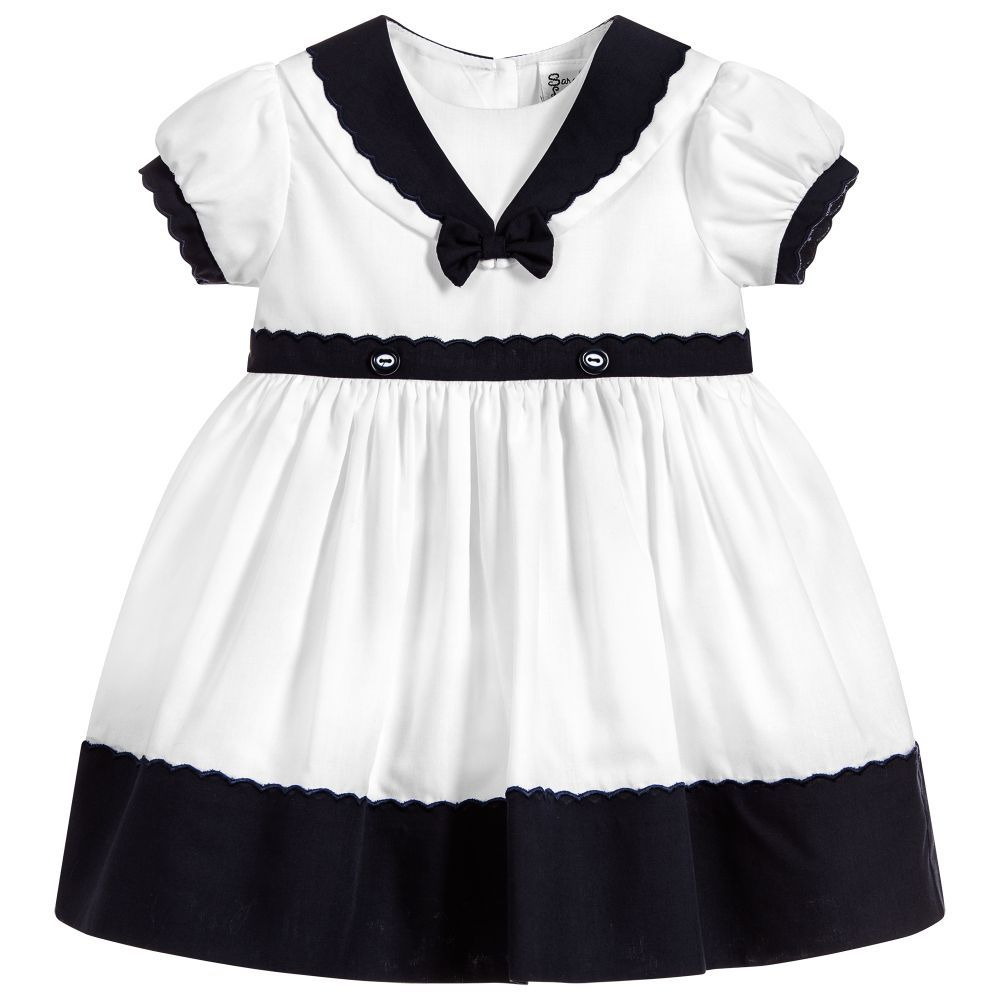 289549f87b23 Younger girls white and navy blue sailor dress by Sarah Louise. Made in a  double layer of soft polycotton. It has a sailor collar and scalloped edged  trim.