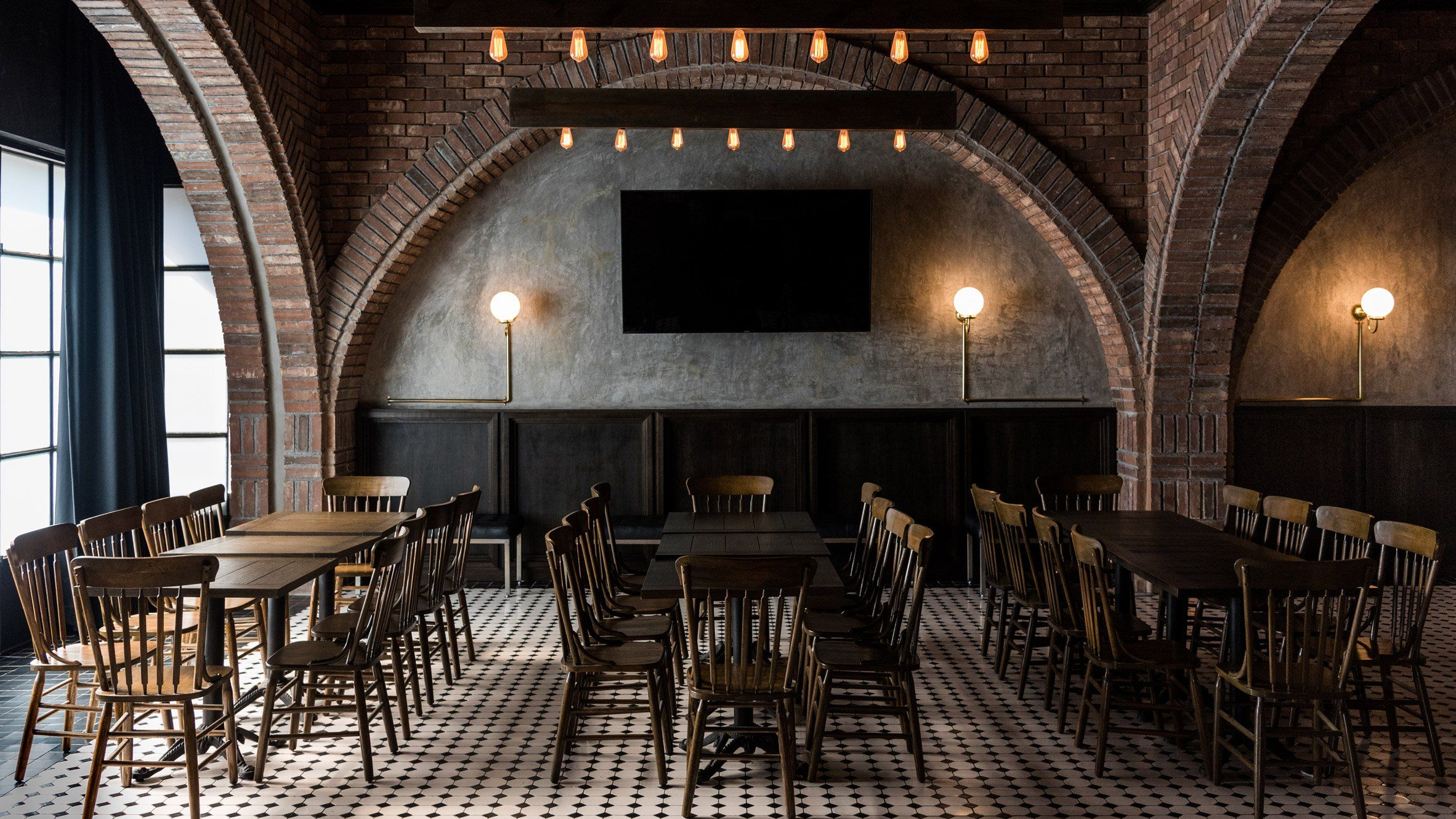 Black and white tiles brick arches wooden furniture