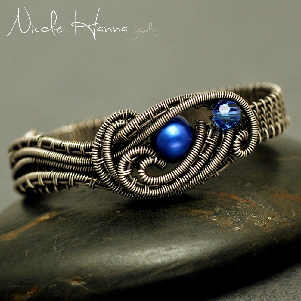 A single blue freshwater pearl is the oceanic focal of this two finger ring. A small blue Swarovski crystal accents the central design of knotted detailed wrapping and weaving. The sterling silver-filled wire is oxidized for depth and detail. Ring fits comfortably with a wide .5 cm woven band, to...