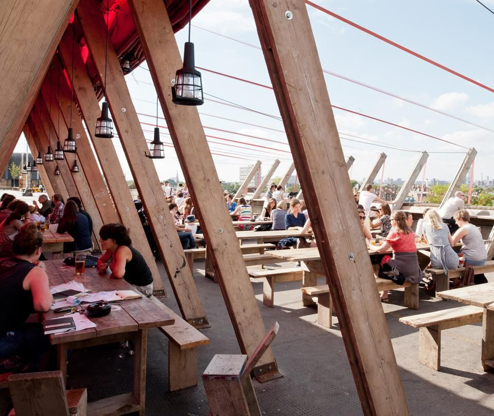 Frank's Cafe, situated on  the roof of a ten story car  park and made of scaffolding  boards, ratchet straps  and red PVC by Practice Architecture