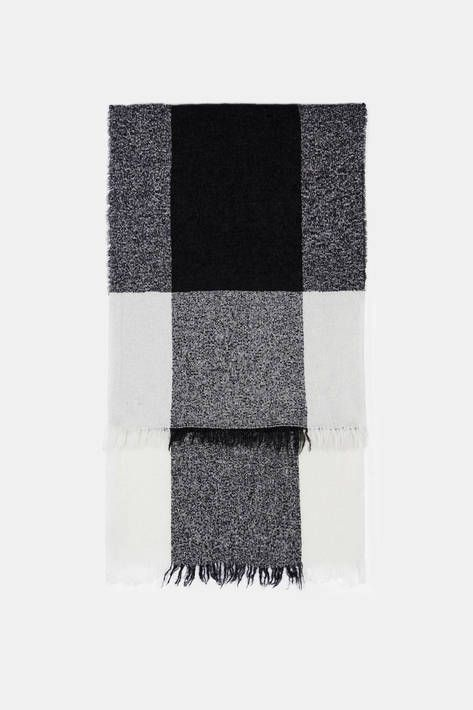 Designed and crafted in Italy from the precious fibers that are a signature of Milan-based Destin, this plush scarf remains incredibly lightweight despite its generous size. The long, narrow rectangle of wool, cashmere, and silk has gently frayed edges that soften the borders of the magnified check pattern in neutral tones of ivory and black.