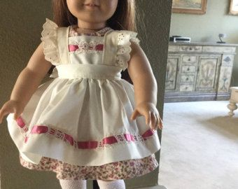 White embroidered dress has pink and white ribbon and bow trim. The hem is trimmed with designer ribbon-flowers. The bodice is fully lined. The back