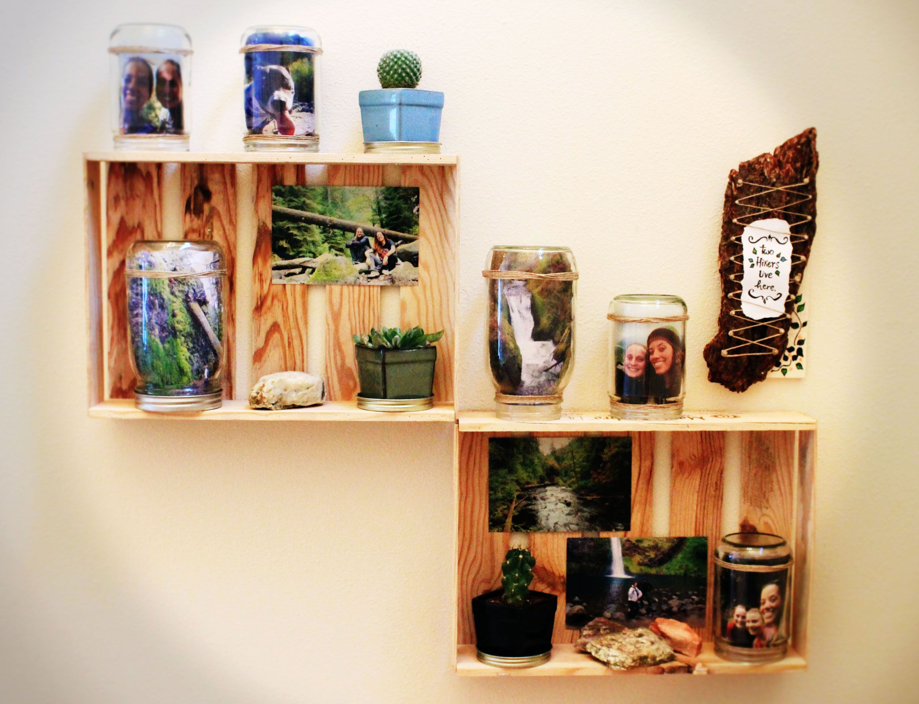 "...And there they are again: the cheese crates! This time as decorative photo shelves with old mason and almond butter jars turned into photo frames. The wooden sculpture to the right goes with the photo stand theme ""two hikers live here"" ~ my roommate and I collected that piece of wood in one of our hikes! :)"