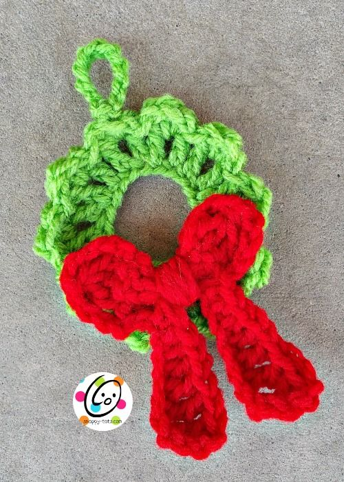 """This wreath, with the cute bow, makes a nice addition to our """"Countdown to Christmas Calendar"""". MATERIALS Yarn: Worsted weight in green and red Crochet Hook: SizeG (pattern calls for a smaller hoo..."""