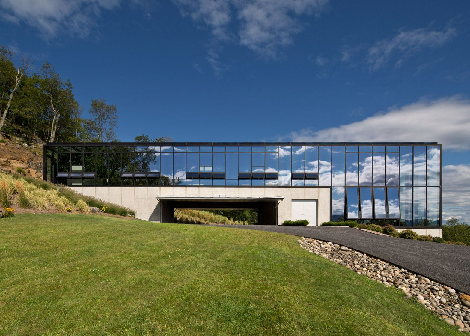 This house in upstate New York features glass walls that reflect the scenic landscape.