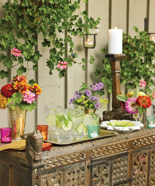 Cookbook author and Indian cooking authority Maya Kaimal decorates a drink station with candles, flowers, and garnishes to create a rustic ambience. Plus: Get Maya Kaimal's summer barbecue menu »   - CountryLiving.com