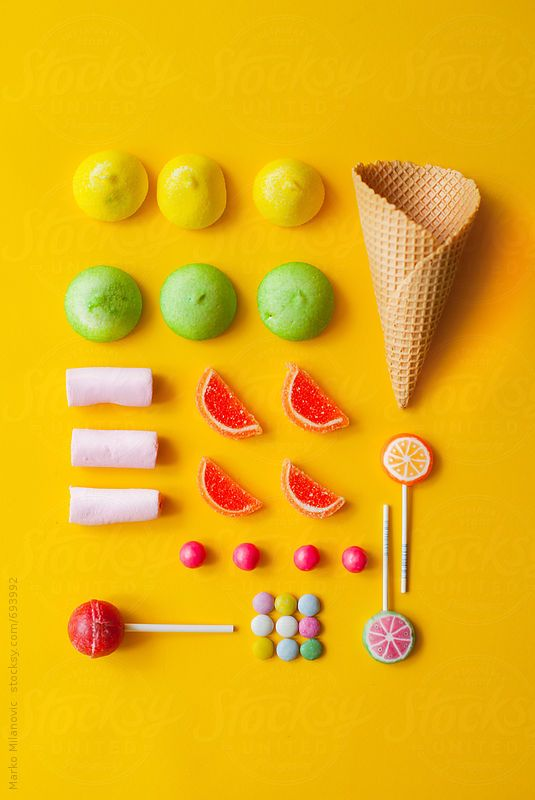 Arranged candies with cone on yellow background by Marko ...