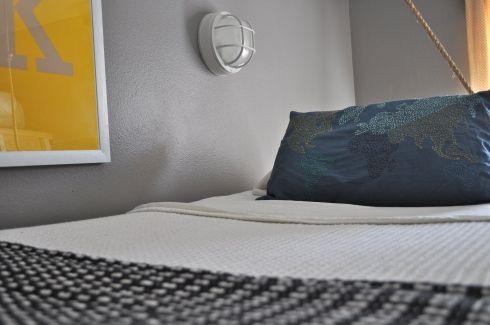 Mỗi giường ngủ được bố trí rất đơn giản với gỗ mộc đóng khung và nệm dày