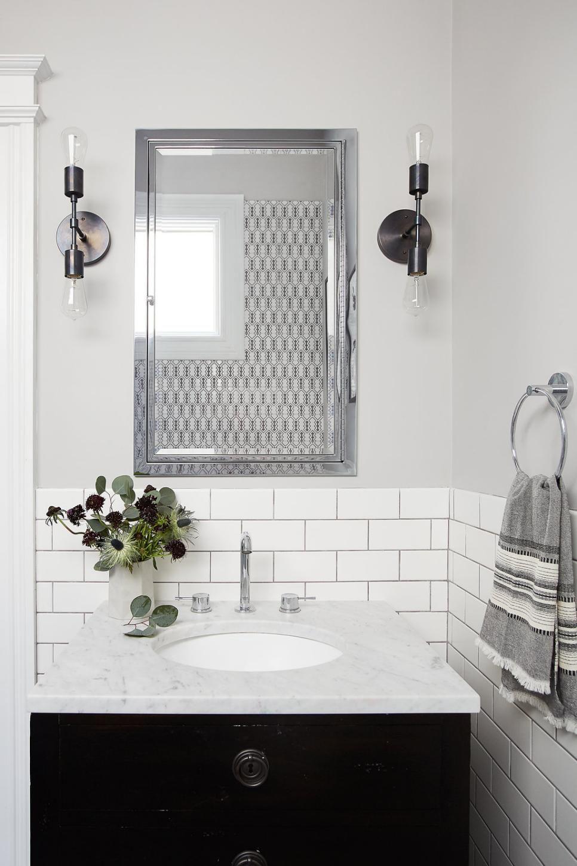 - Bathroom With Marble-Top Black Vanity And Tile Backsplash Powder