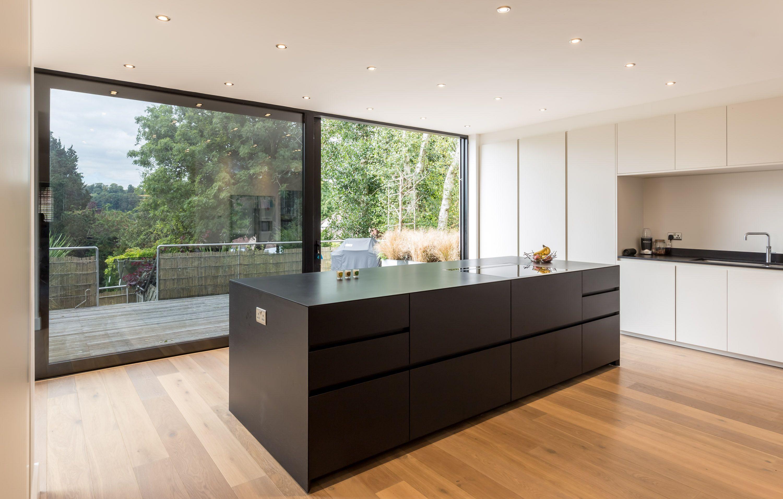 Sleek black kitchen island large sliding glass door to