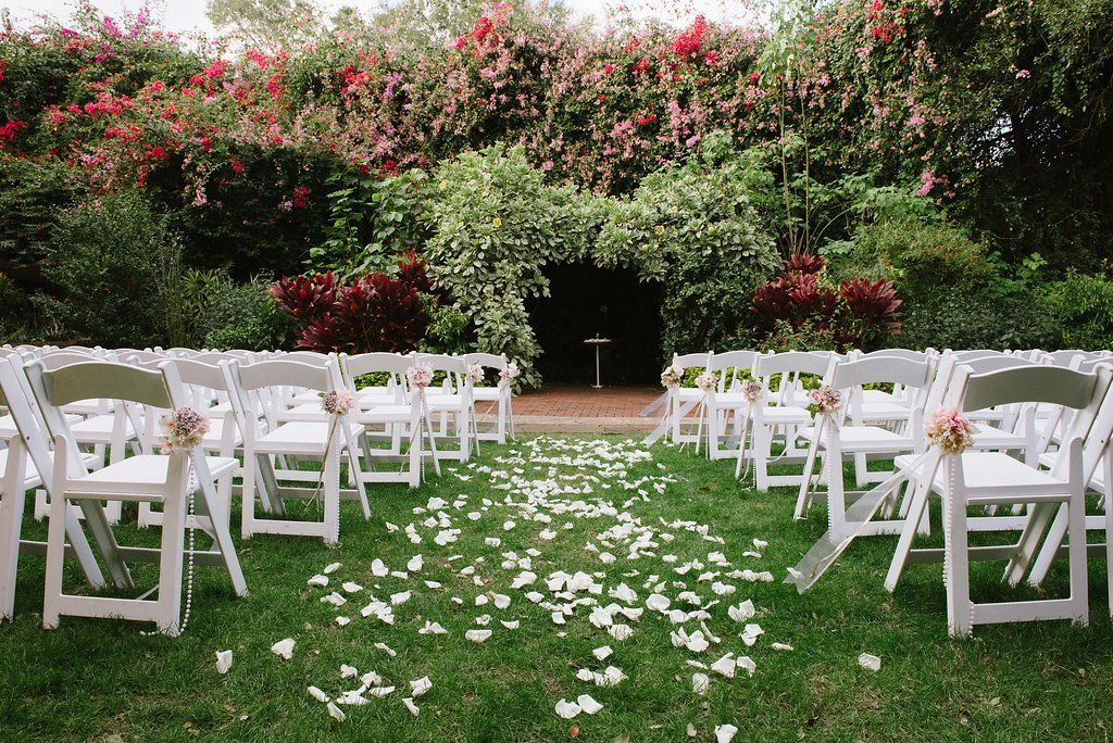 Outdoor Garden Wedding Ceremony Decor With White Folding Chairs