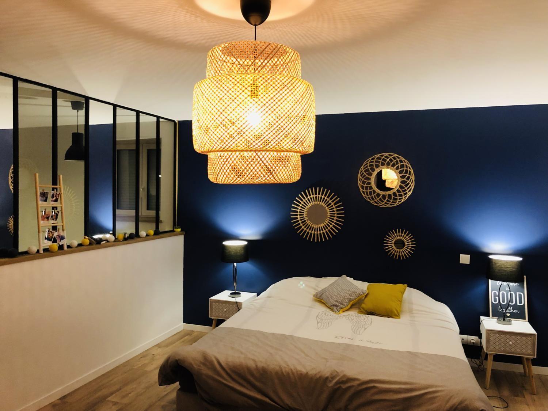 Déco chambre avec un mur bleu nuit, abat jour en osier et une