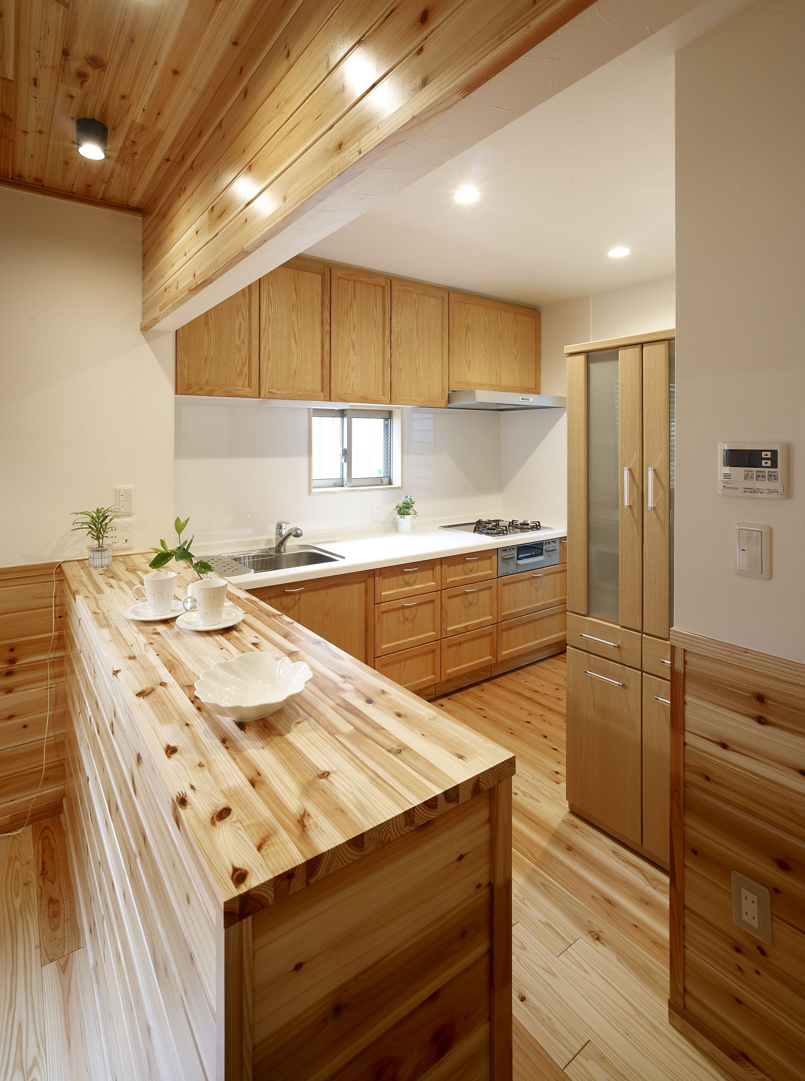 ずっと憧れていたログハウス風の住まいにリノベーション 木目の綺麗な框扉のキッチン は台輪まで引出しタイプのフロアキャビネットでたっぷり収納できます 床 壁 天井には杉の無垢材をふんだんに用いました メンテナンスのしやすさを考慮し 汚れ防止のクリア塗装で