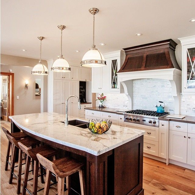 """""""Designer @madisontaylor_inc chose a Wild Rice perimeter to compliment the #gorgeous #wooden hood, trim, island base and stools in this warm #kitchen."""""""