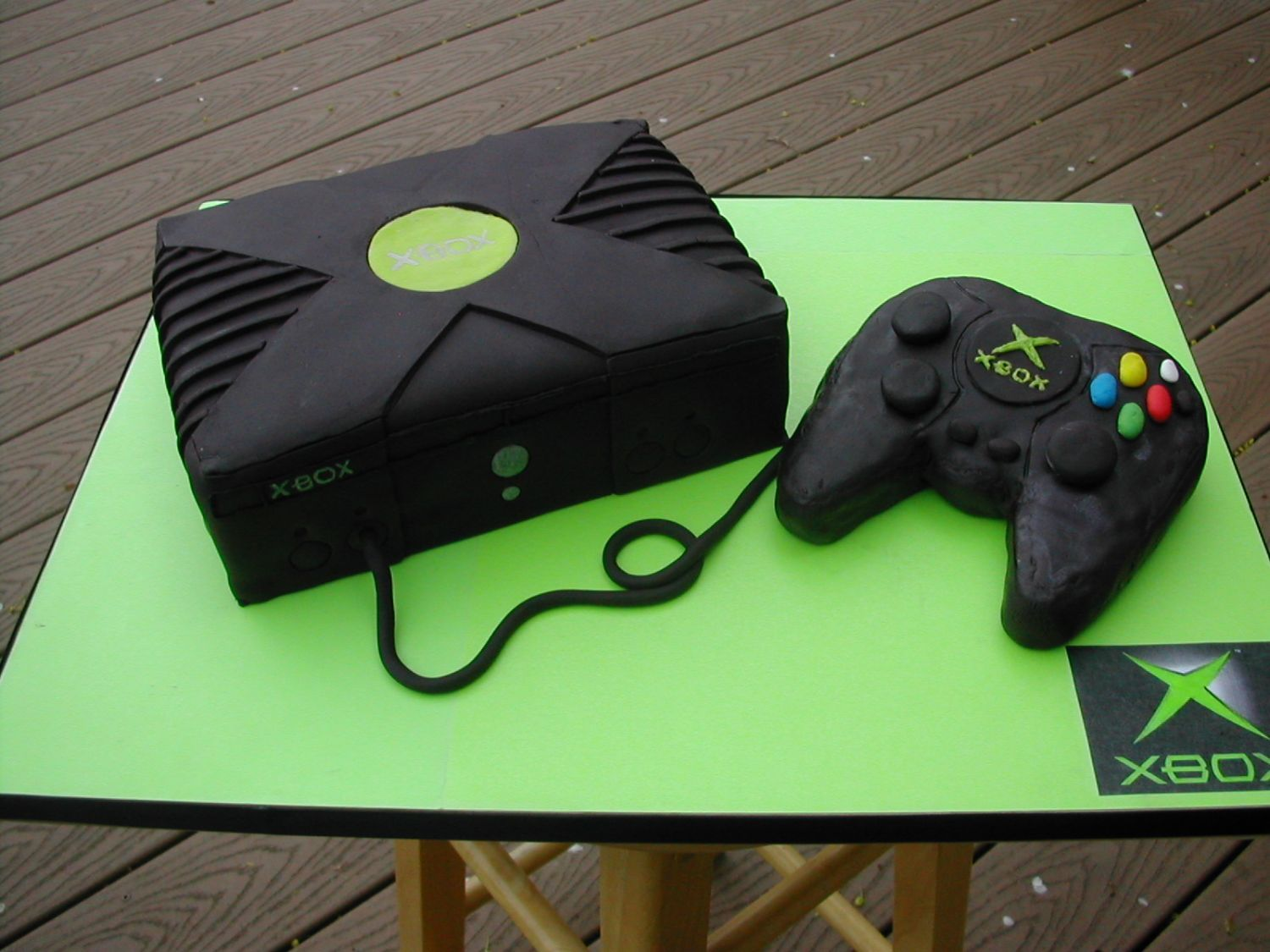 Xbox cake white cake with neon green buttercream filling covered in satin ice black vanilla fondant controller is carved rice crispy