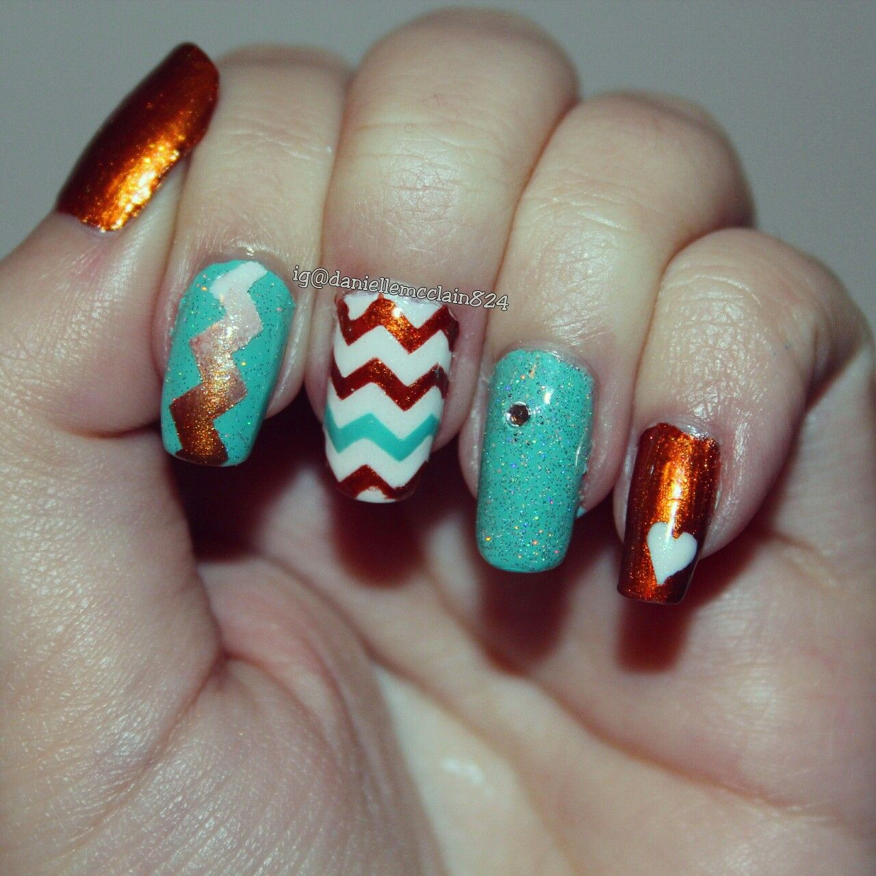 a fun and colorful nail art design with chevrons, a heart with a ...