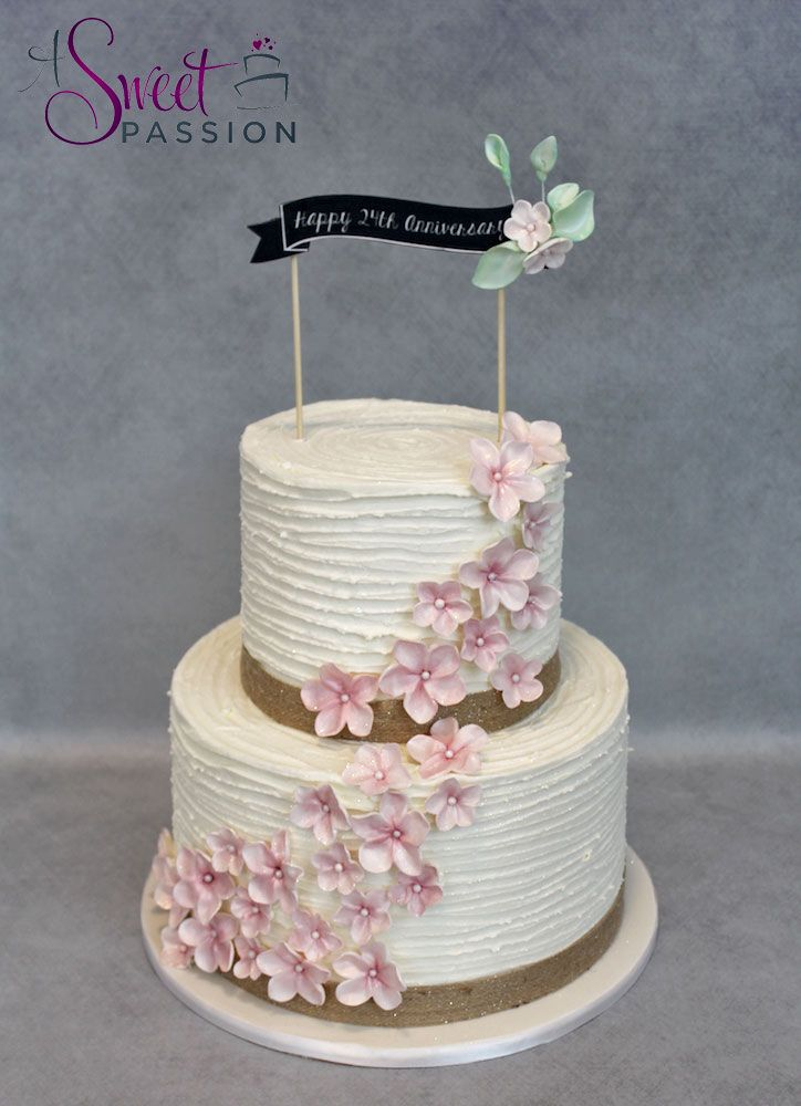 This rustic buttercream cake features a custom topper and cascading cherry blossoms.    www.asweetpassion.com