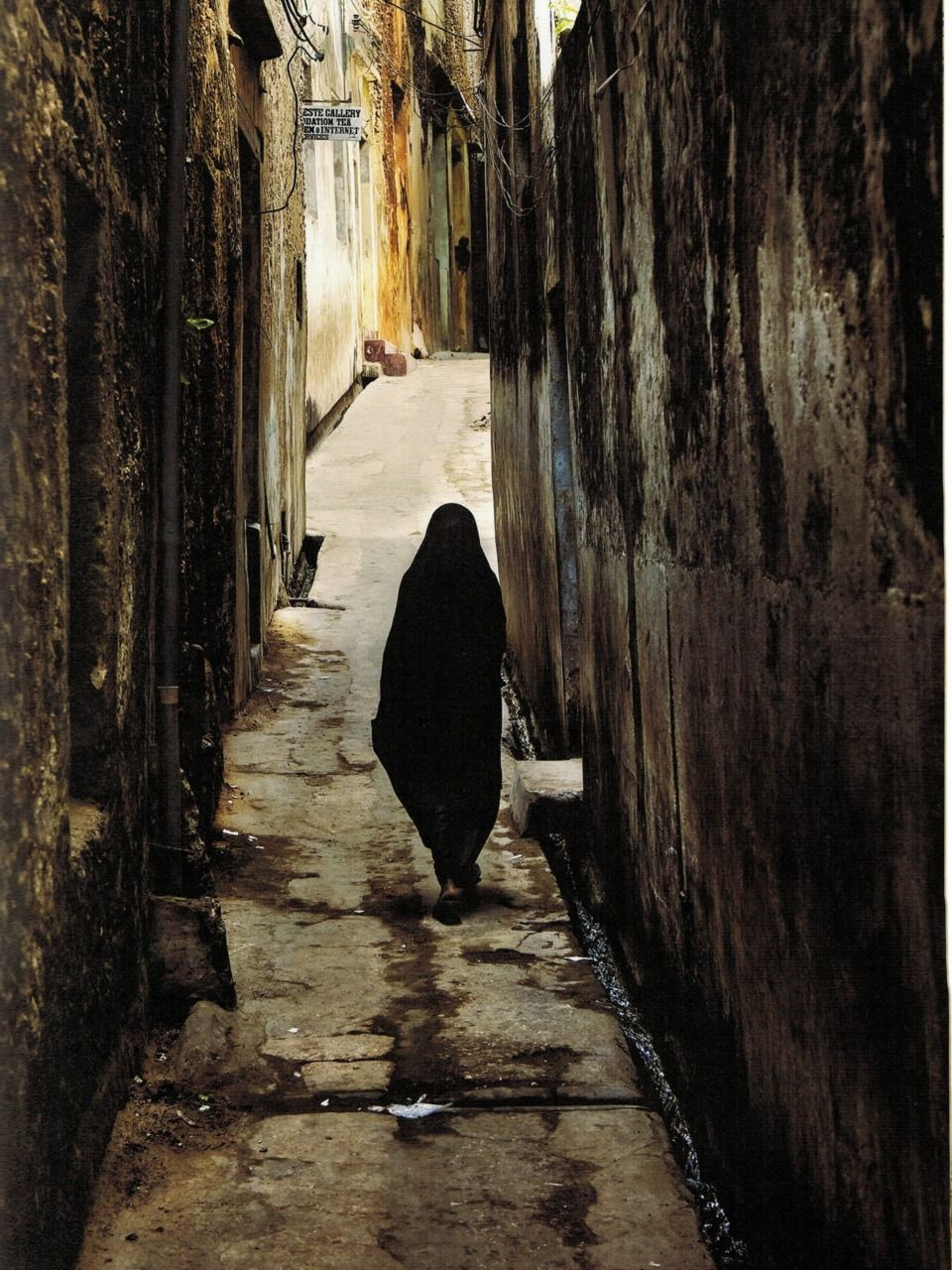 A woman wearing a bui-bui (long black veil) makes her way home along a narrow street leading from the seafront to the oldest part of Lamu Town, called Mkomani. Doors within small covered porches, called daka, protect the entry to the houses where the women are secluded.      from Lamu: Kenya's Enchanted Island