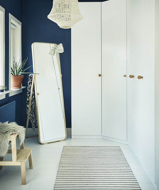 A wall of white wardrobes and a mirror in a dark blue room