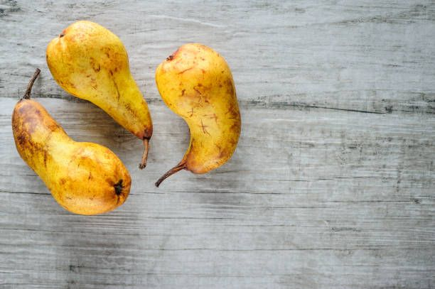 yellow pears on white wooden background top view