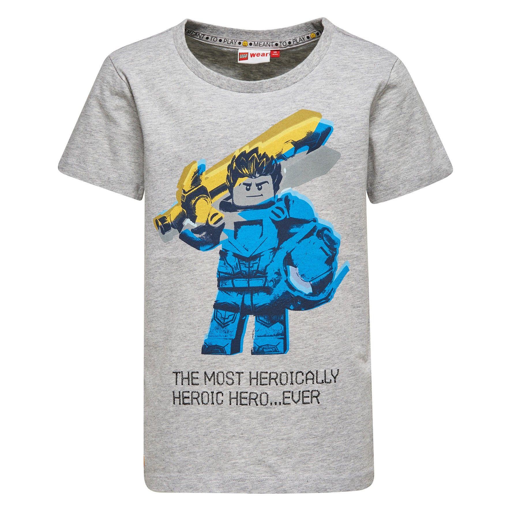 Licht grijze jongens tshirt TEO van het merk Legowear. Dit is een tshirt met een ronde hals en korte mouwen. De shirt komt uit de reeks Lego Knexo Knights De shirt heeft een print van een groot Lego ventje met bijhorende tekst.