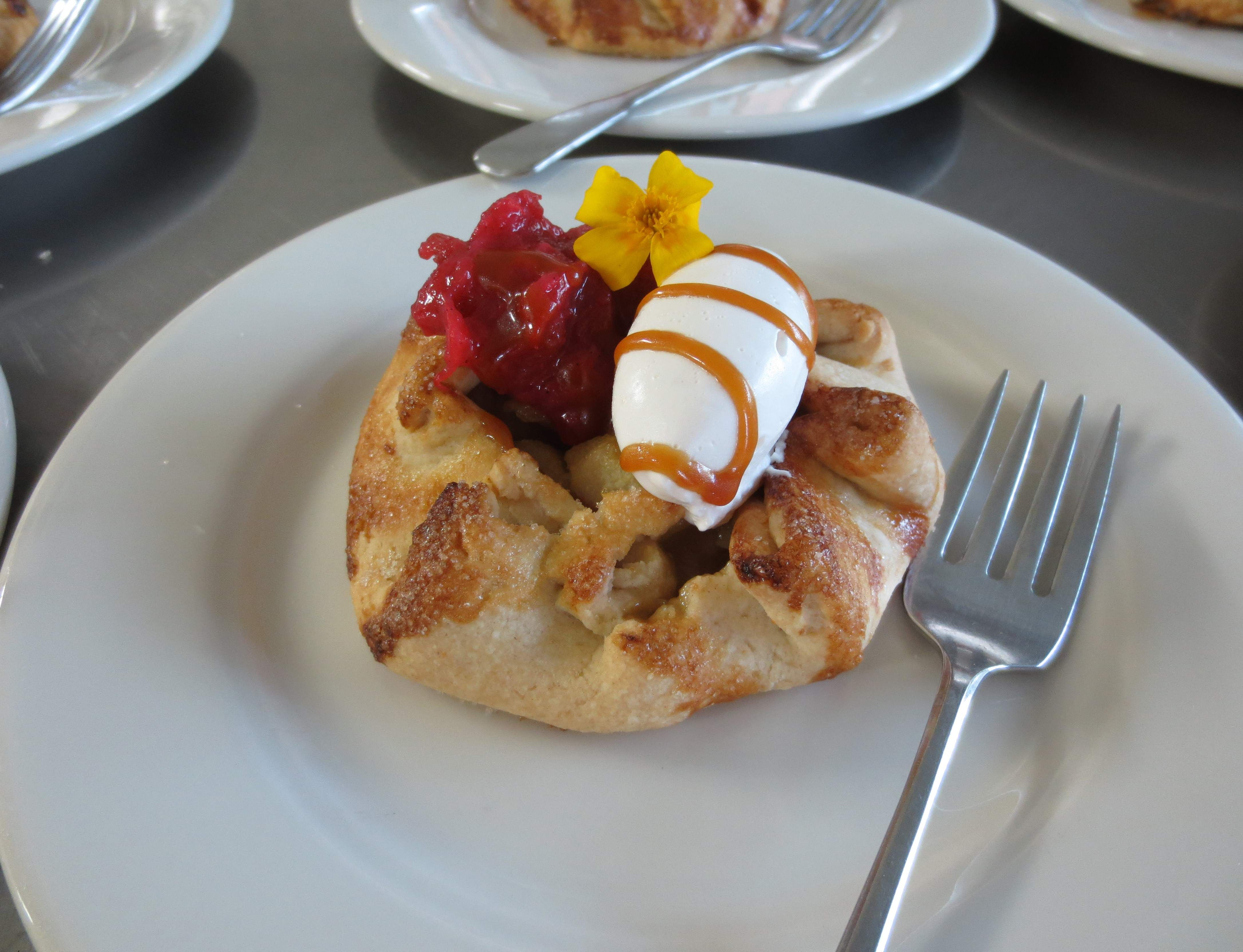 Pear Gallette topped with Rhubarb Compote, whipped cream, marigolds grown in our greenhouse and drizzled with Alaska Birch Syrup Caramel Sauce.