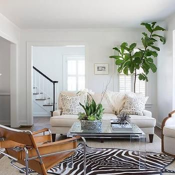 Zebra Rug Layered Over Gray Bound Sisal Rug With Lucite Coffee Table Hide Rug Living Room Cowhide Rug Living Room Rugs In Living Room
