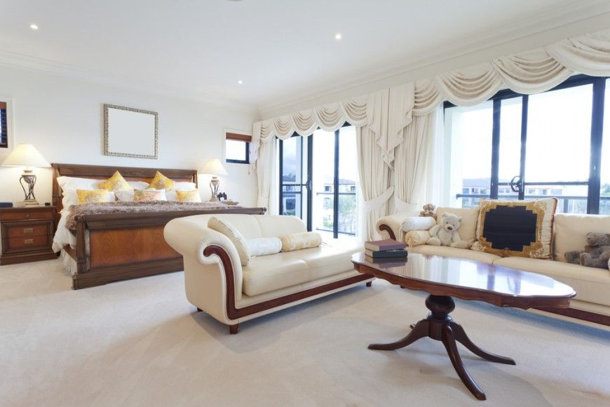 a light and bright master bedroom with a large sofa and chaise