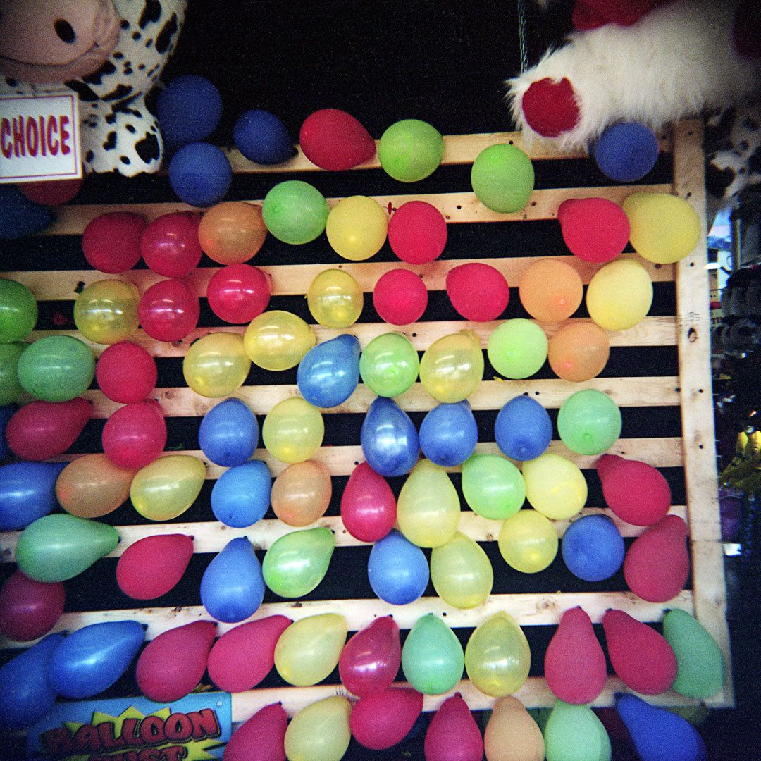 balloons stapled to a wooden pallet for a game koohl county fair